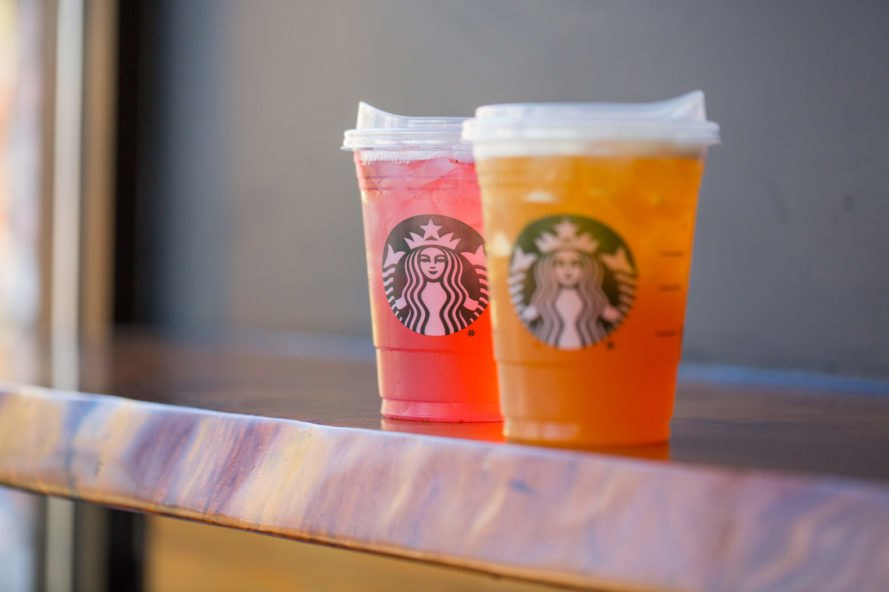 Two beverages in Starbucks cups with plastic, strawless lids similar to hot coffee lids