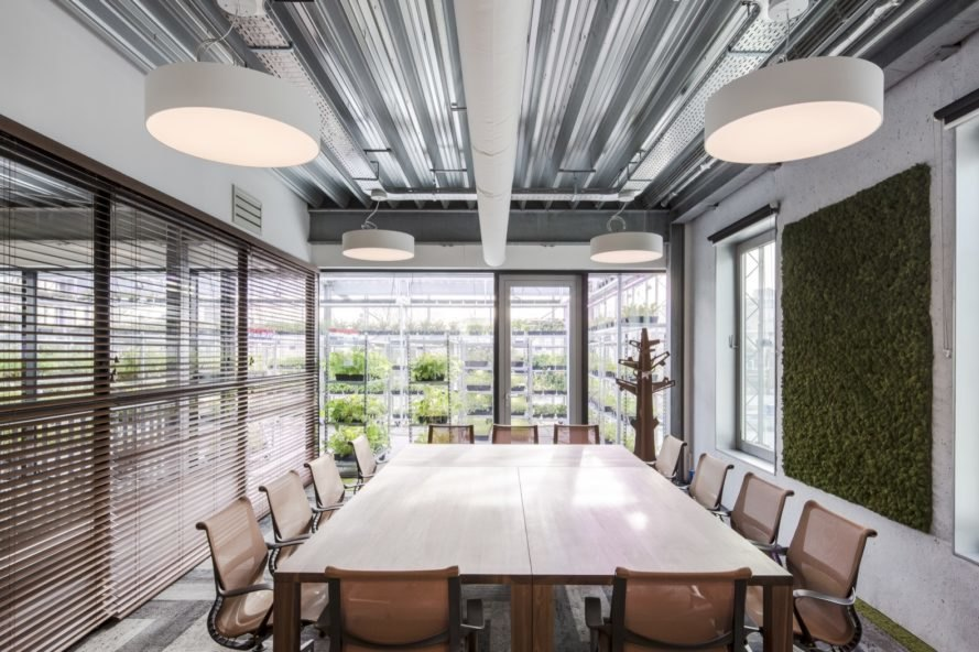 meeting room with large table, several chairs and a greenery wall