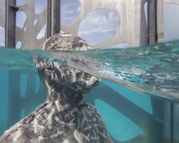 humanoid sculpture partially submerged in ocean water
