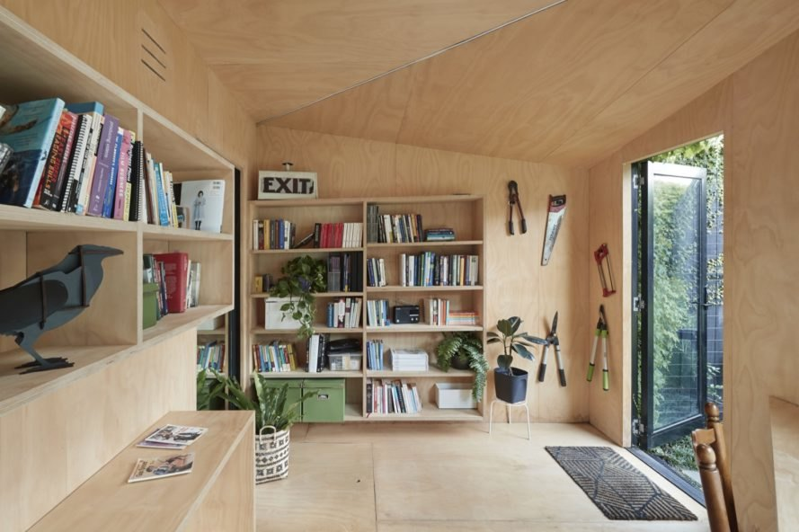 interior workspace with large bookshelf, hanging garden tools and potted plants