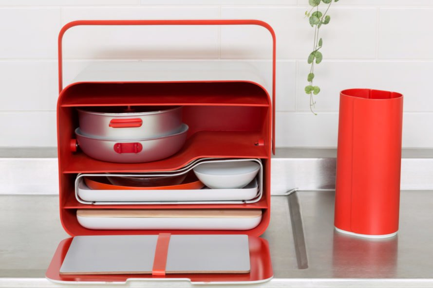 A red box with kitchenware such as pots, a cutting board and a thin hotplate