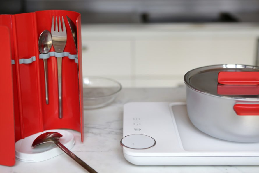 Red wrap holding silverware and a white cooktop with a silver and red pot on top
