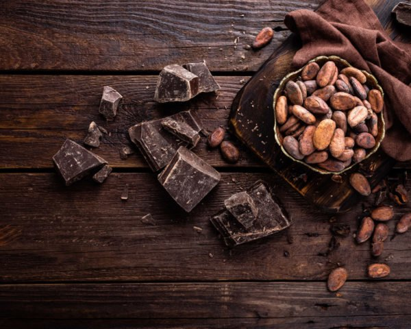 Dark chocolate and cocoa beans on dark wood background