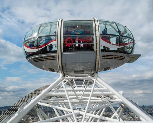 Tourists riding in a pod of the London Eye with Coca Cola ads on the pod