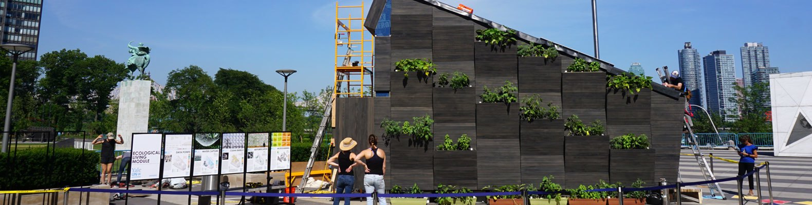Two people standing outside looking up at plants growing on the exterior wall of a tiny home