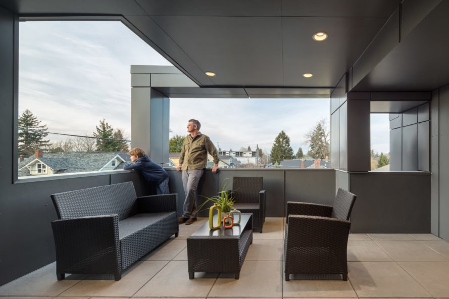 man on exterior deck with furniture and city views