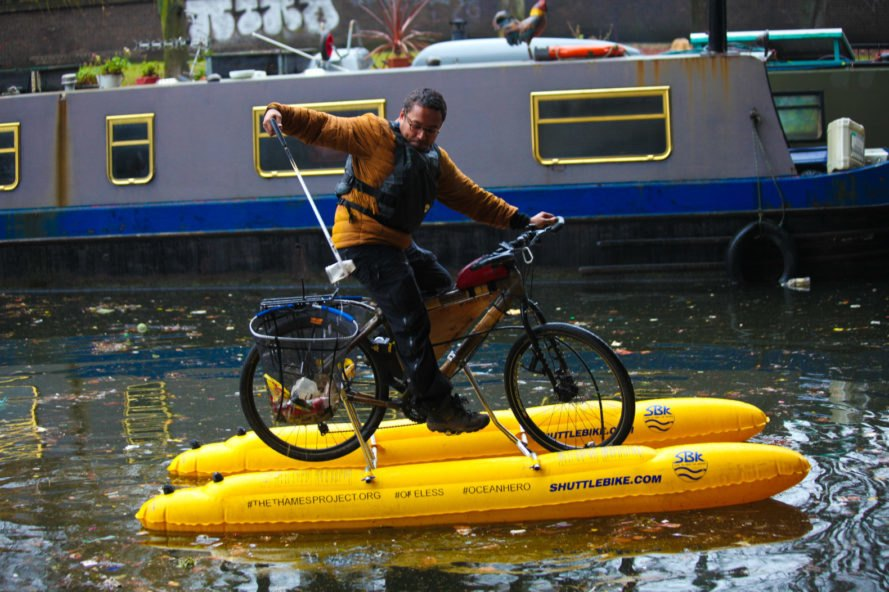Man grabbing trash from the river while on a floating bike