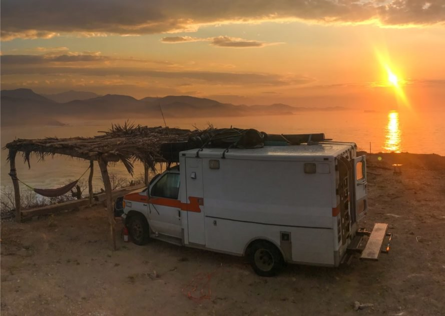 an old ambulance parked in front of a sunset
