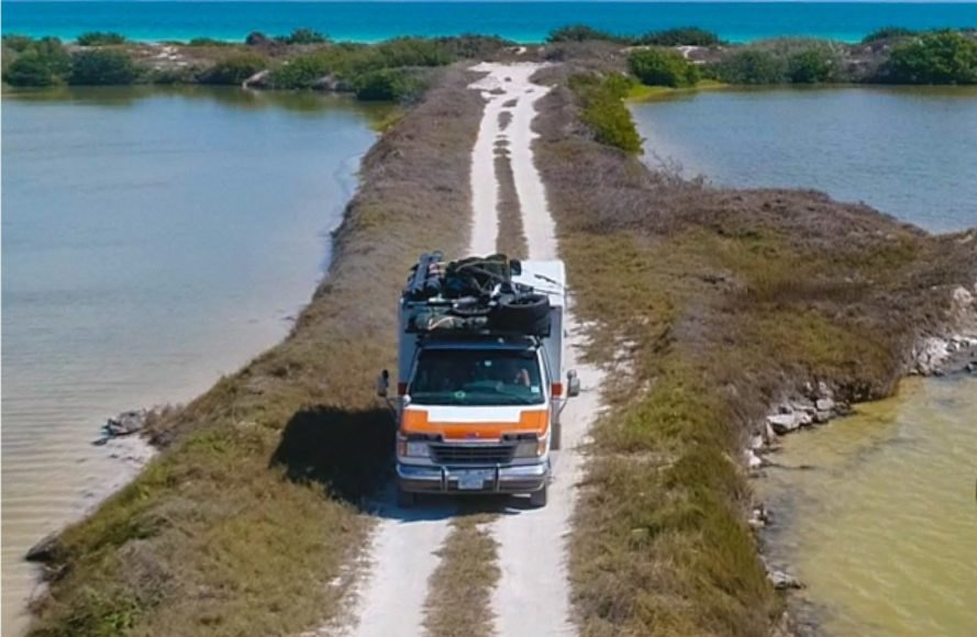a reformed ambulance on a dirt road surrounded by ocean