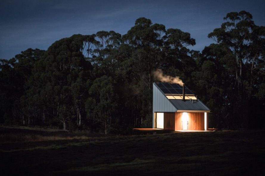 night image of tiny cabin with smoke coming out of the chimney