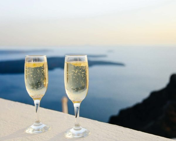 two champagne glasses on a balcony overlooking the sea
