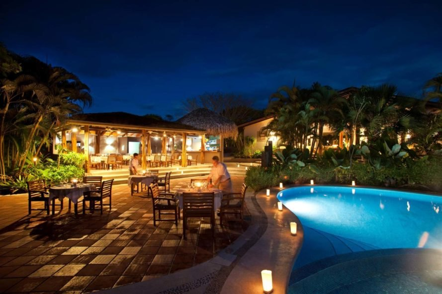 luxury hotel outdoor patio with swimming pool at night