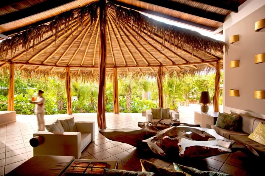 interior of thatched gazebo with lounge chairs