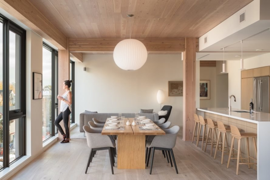 dining space with round hanging lamp, long wood table and gray chairs