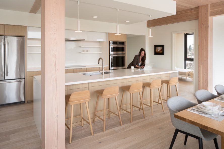 woman leaning over white kitchen counter with several timber bar stools