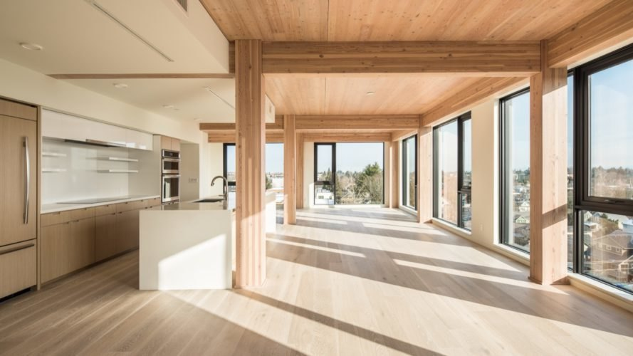 open plan living space with timber ceilings, large windows and a kitchen with a white island