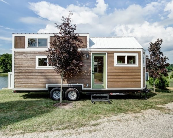 a tiny home on wheels with light wood siding and pastel green door