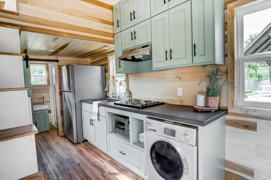 a kitchen with light green cabinets and a washing machine