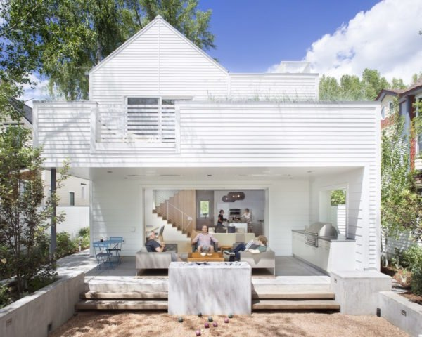 People lounging on outdoor deck space behind a white home