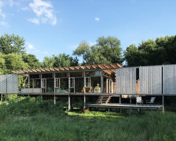 Timber and glass cabin raised on stilts surrounded by grass and trees