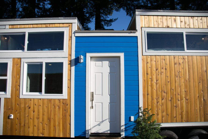 tiny wooden home with blue entranceway and white door