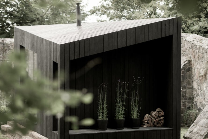 black cabin with three large plants in a narrow space