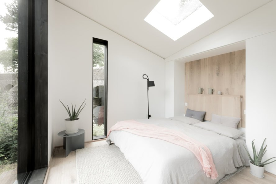 an all-white bedroom witha large bed and skylight