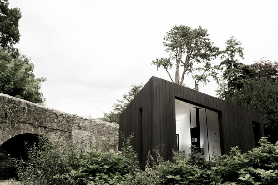 black cabin with large glass window