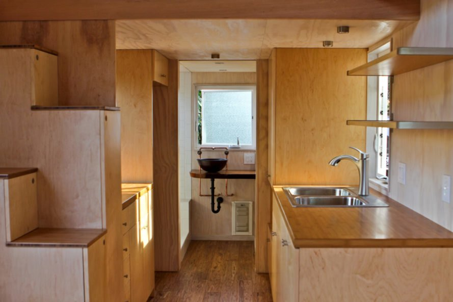 a wooden kitchen and bathroom in the background