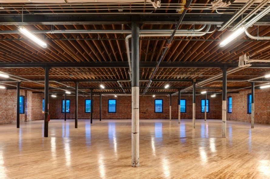 open floor space in renovated warehouse with light wood floors and brick walls