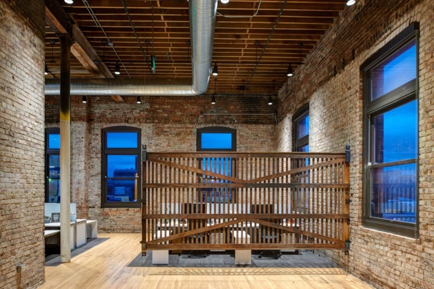 office space with brick walls and a slatted wood divider