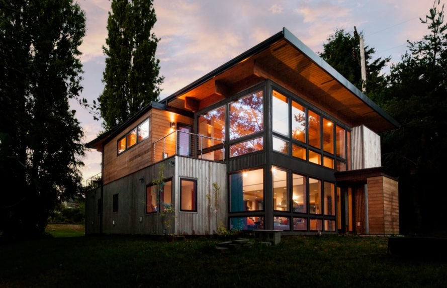 angled view of home with corrugated metal exterior and several windows at dusk