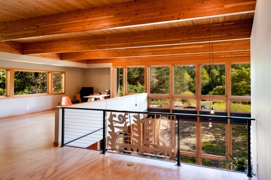 Light wood landing area on second floor with wood ceilings and exposed beams