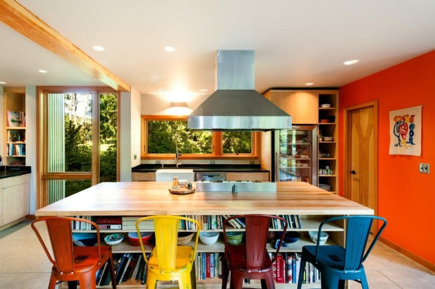 light wood kitchen island with an oven vent hood above and four different colored bar stools
