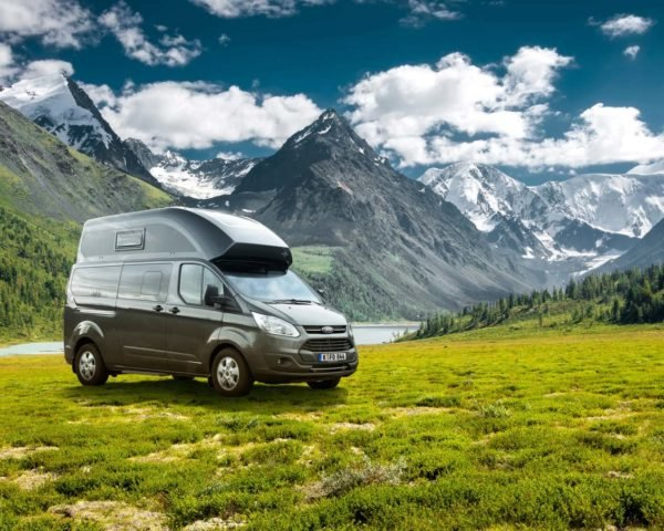 black van against a background of mountains, lake, and green meadows