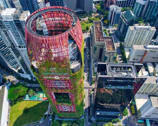 aerial view of tower with red mesh cladding and greenery