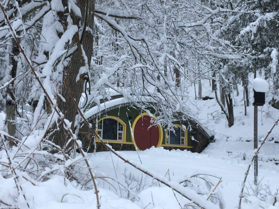 green hobbit home covered in snow