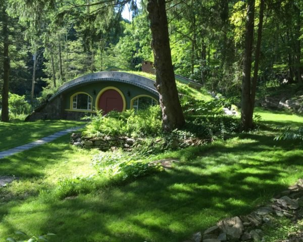 green hobbit home with curved green roof