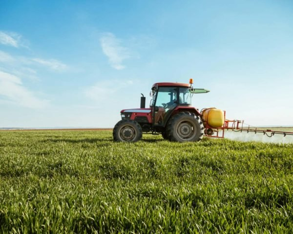 tractor spraying pesticide on a green wheat field under a blue sky
