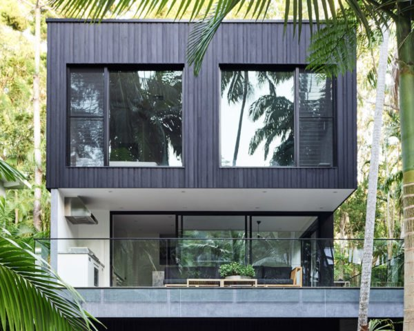 Multi-story black home with large windows surrounded by rainforest