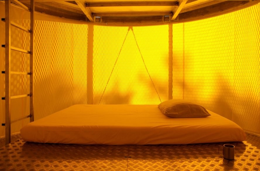 yellow-hued interior with bed on the floor