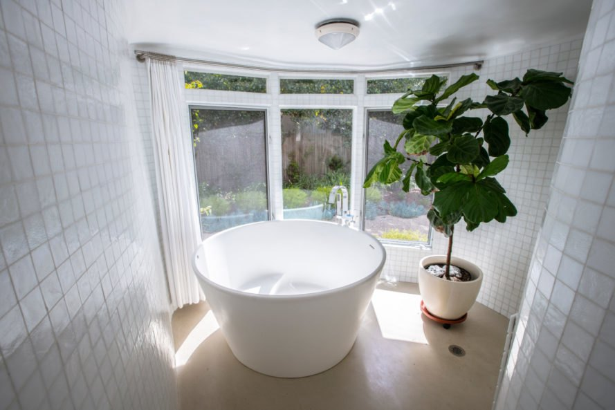a white round bathtub with view of gardens