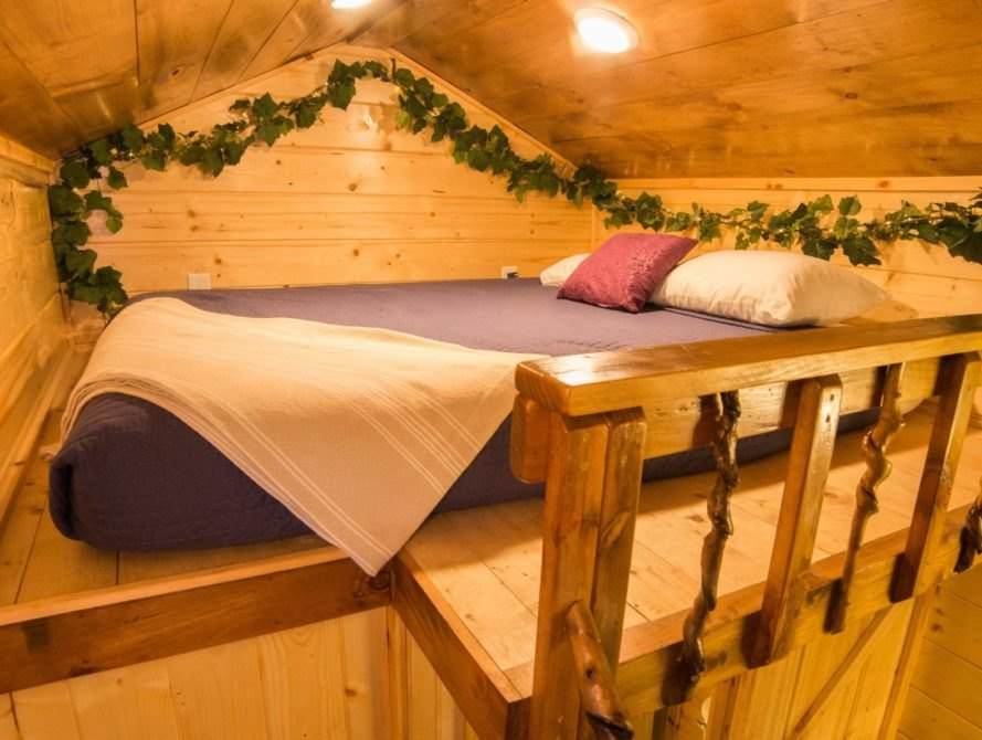 a sleeping loft with queen sized bed