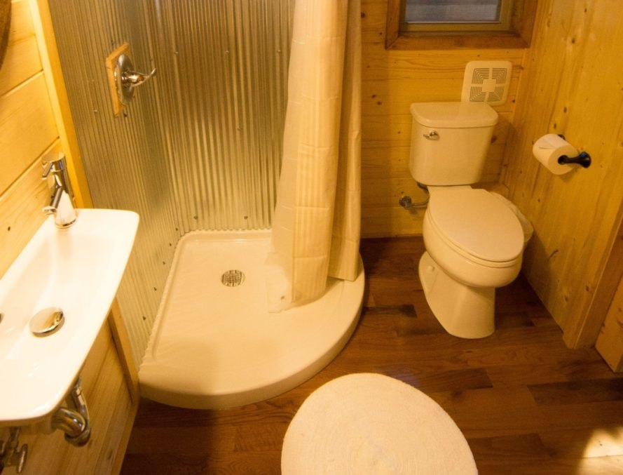 a bathroom with shower, toilet and sink