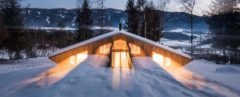 wood mountain chalet lit from within at night on a snowy landscape