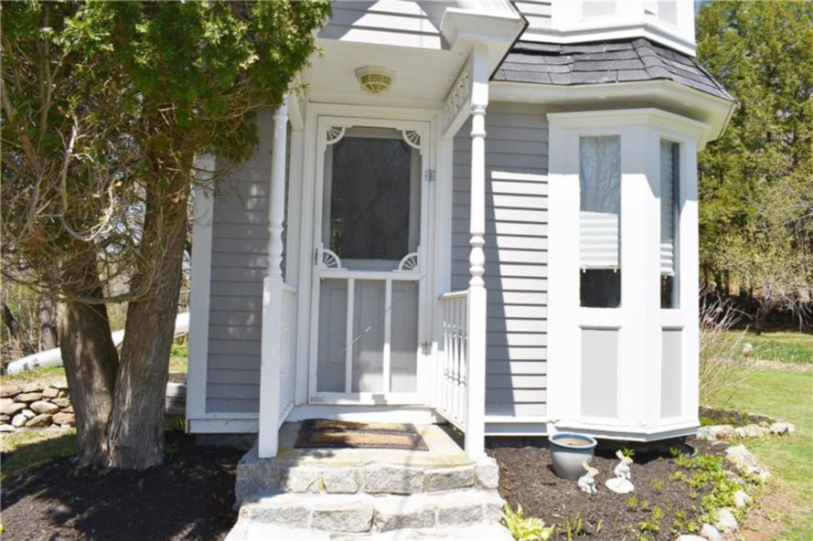 front door of white victorian tiny home