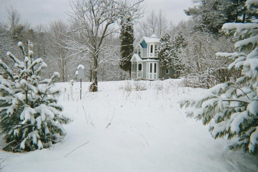 white victorian tiny home in snowy landscape
