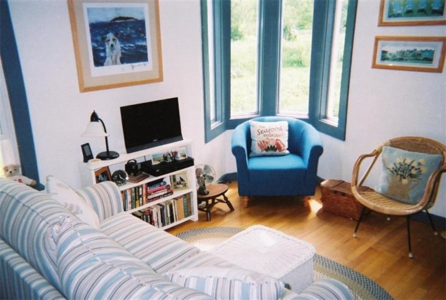living room with striped sofa and blue chair