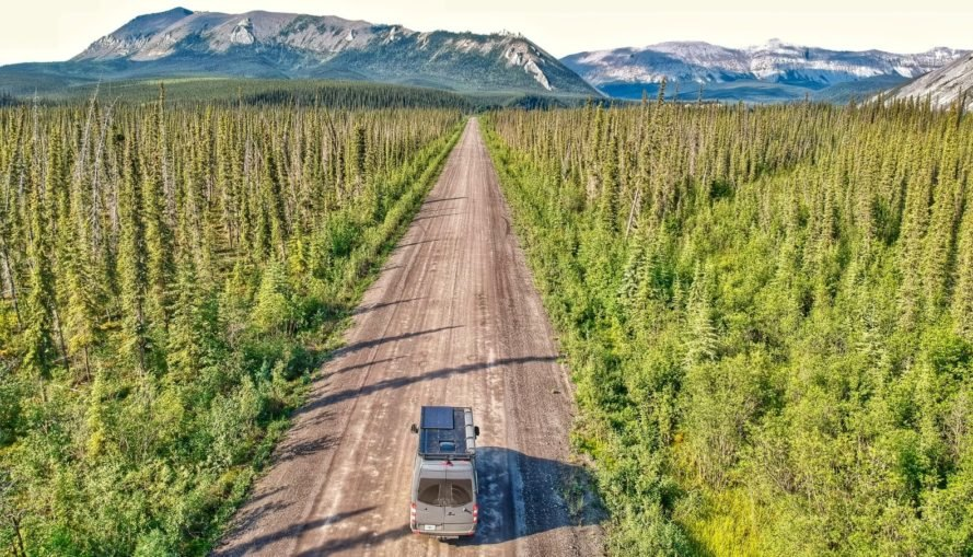 van in middle of dirt road surrounded by forest