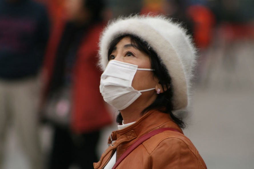 Woman looking to sky and wearing white mask over nose and mouth